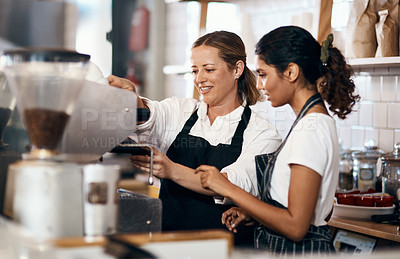 Buy stock photo Shot of two women preparing coffee in a cafe