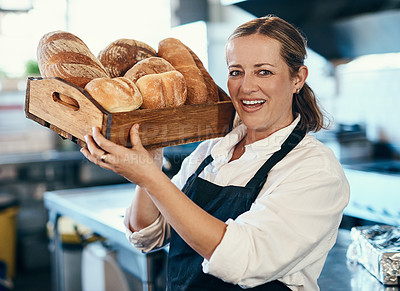 Buy stock photo Shot of a mature woman holding a selection of freshly baked breads in her bakery