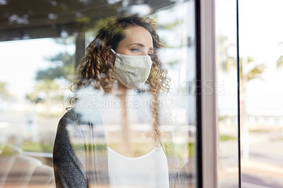 Buy stock photo Shot of a young woman wearing a mask and looking pensively out of a window at home