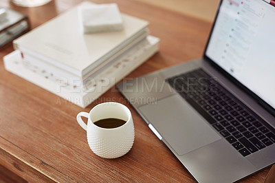 Buy stock photo Shot of a laptop and cup on a coffee table at home