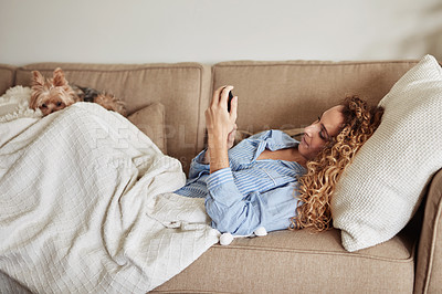 Buy stock photo Shot of a young woman using a smartphone while relaxing on the sofa at home with her dog