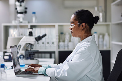 Buy stock photo Cropped shot of an attractive young female scientist working on a laptop in her laboratory