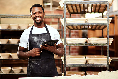 Buy stock photo Cropped shot of a man using a digital tablet while working in a bakery