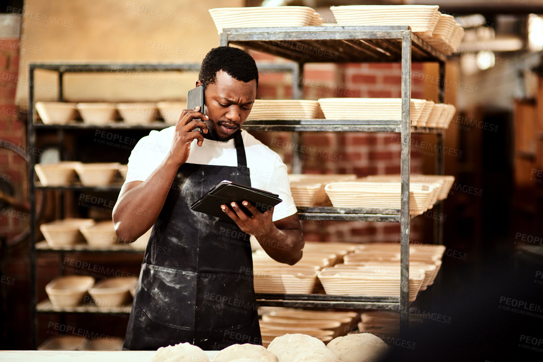 Buy stock photo Cropped shot of a male baker talking on the phone while using a digital tablet at work