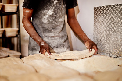 Buy stock photo Cropped shot of a male baker busy shaping dough at work