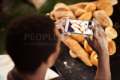 Buy stock photo Cropped shot of a male baker taking a picture on his cellphone of a selection of freshly baked bread