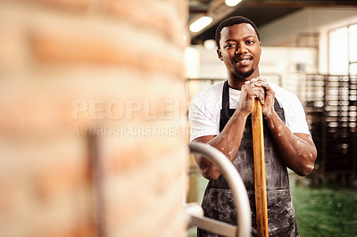 Buy stock photo Shot of a confident young man working in a bakery