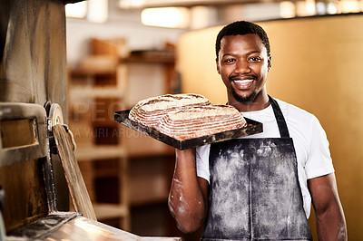 Buy stock photo Cropped shot of a male baker holding up freshly baked bread in his bakery
