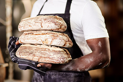 Buy stock photo Cropped shot of a male baker holding freshly baked bread in his bakery