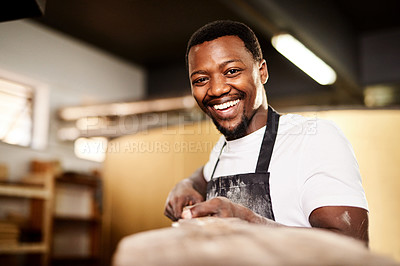 Buy stock photo Cropped shot of a male baker removing freshly baked bread from the oven