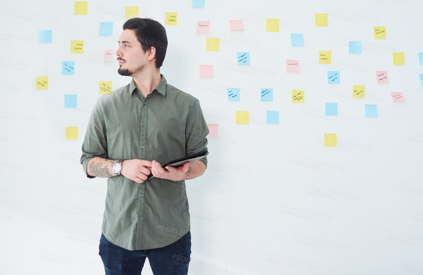 Buy stock photo Shot of a young businessman using a digital tablet while standing against a wall with notes in an office