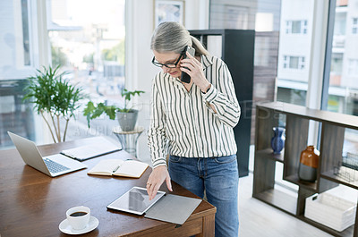 Buy stock photo Shot of a mature businesswoman talking on a cellphone while using a digital tablet in an office