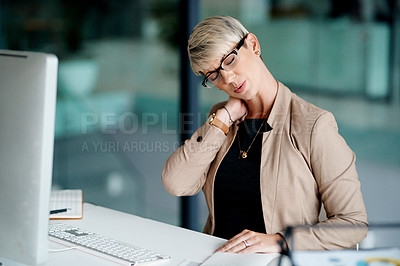 Buy stock photo Shot of a young businesswoman suffering with neck pain while working in an office