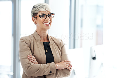 Buy stock photo Shot of a young businesswoman standing with her arms crossed in an office