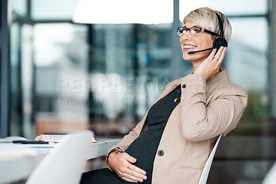 Buy stock photo Shot of a pregnant businesswoman wearing a headset while working in an office