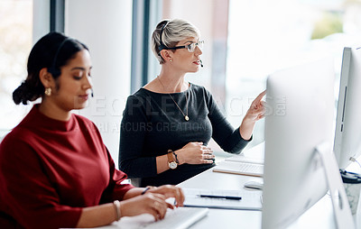 Buy stock photo Shot of a young businesswoman wearing a headset while working on a computer alongside a colleague in an office