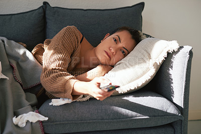 Buy stock photo Shot of an attractive young woman relaxing on the sofa and watching television at home