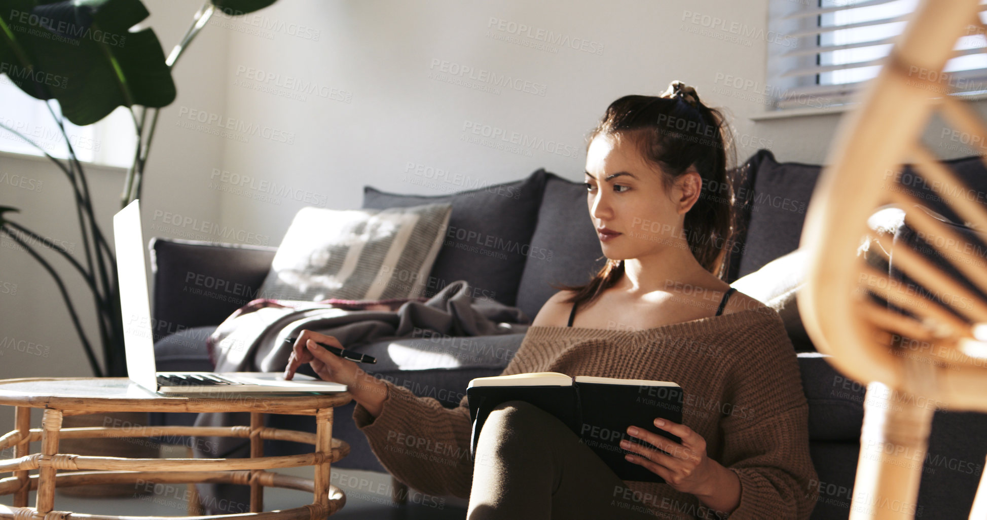 Buy stock photo Shot of an attractive young woman writing notes and using a laptop while working from home