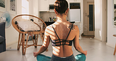 Buy stock photo Rearview shot of a young woman meditating while practising yoga at home
