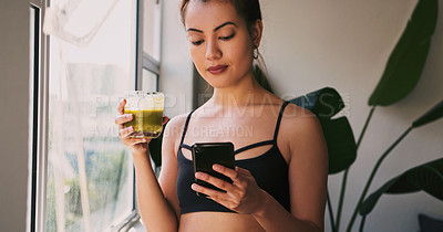 Buy stock photo Shot of a young woman using a cellphone while drinking a green juice at home