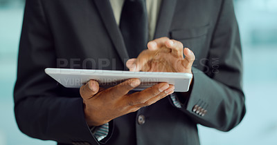 Buy stock photo Cropped shot of an unrecognisable businessman using a digital tablet in a modern office