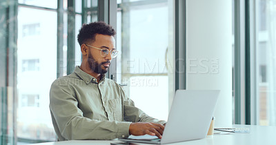 Buy stock photo Shot of a young businessman using a laptop in a modern office