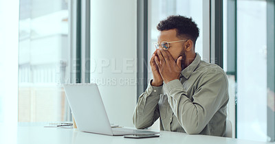 Buy stock photo Shot of a young businessman looking stressed while using a laptop in a modern office