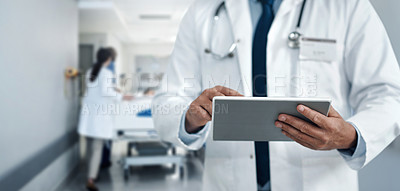 Buy stock photo Cropped shot of an unrecognisable doctor using a digital tablet in a modern hospital