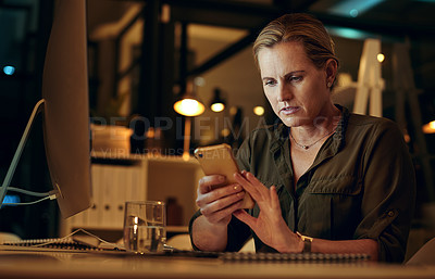Buy stock photo Shot of a woman using her cellphone while sitting at her desk at night