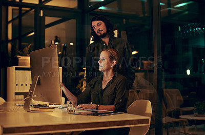 Buy stock photo Shot of two businesspeople looking at something on a computer in an office at night