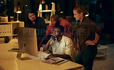 Buy stock photo Shot of a group of businesspeople looking at something on a computer in an office at night