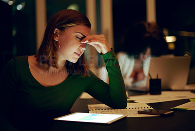 Buy stock photo Shot of a businesswoman suffering with a headache while working late
