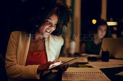 Buy stock photo Shot of a businesswoman using a digital tablet in an office at night