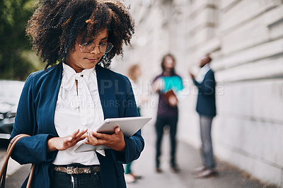 Buy stock photo Shot of a businesswoman holding a digital tablet while walking through the city