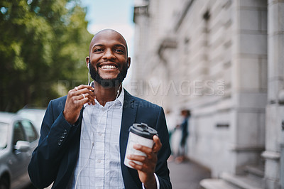 Buy stock photo Shot of a businessman holding a coffee and listening to music through earphones while walking through the city