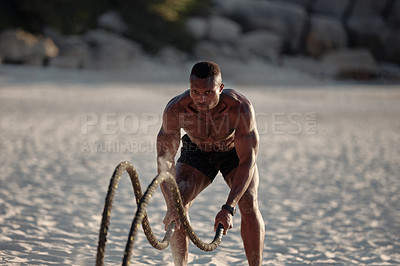 Buy stock photo Shot of a muscular young man exercising with battle ropes at the beach