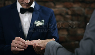 Buy stock photo Cropped shot of two men exchanging rings on their wedding day