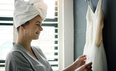 Buy stock photo Shot of a woman admiring her wedding dress before putting it on