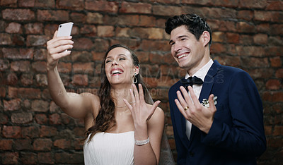 Buy stock photo Shot of a young newlywed couple showing off their rings while on a video call