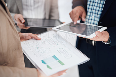 Buy stock photo Closeup shot of a group of unrecognisable businesspeople analysing graphs in an office