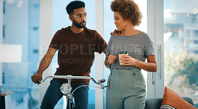 Buy stock photo Shot young designer talking to a colleague while riding a bicycle in an office