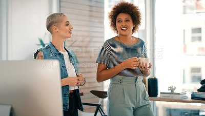 Buy stock photo Shot of two young designers chatting while walking through an office together