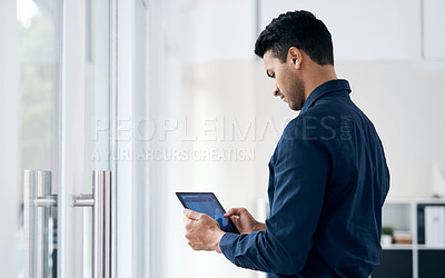 Buy stock photo Shot of a young businessman using a digital tablet to analyse financial data in a modern office
