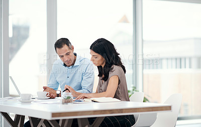 Buy stock photo Shot of a businessman and businesswoman going over paperwork in a modern office