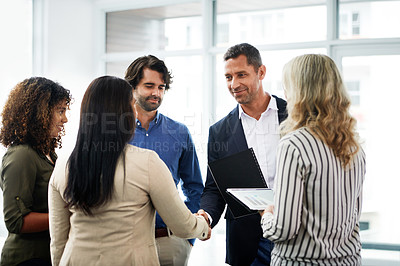 Buy stock photo Shot of a businessman and businesswoman shaking hands during a meeting in a modern office