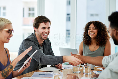 Buy stock photo Shot of two young businessmen shaking hands during a team meeting in a modern office