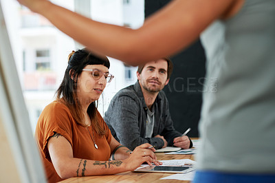 Buy stock photo Shot of a young businesswoman using a digital tablet during a presentation in a modern office