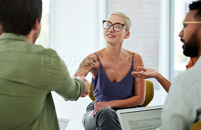 Buy stock photo Shot of a young businesswoman and businessman shaking hands during a team meeting in a modern office