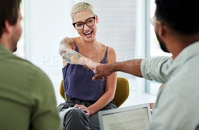 Buy stock photo Shot of a young businesswoman and businessman fist bumping during a team meeting in a modern office