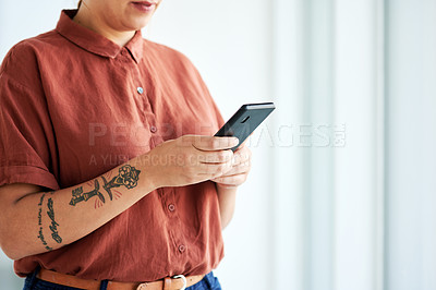 Buy stock photo Cropped shot of a businesswoman using her cellphone at the office